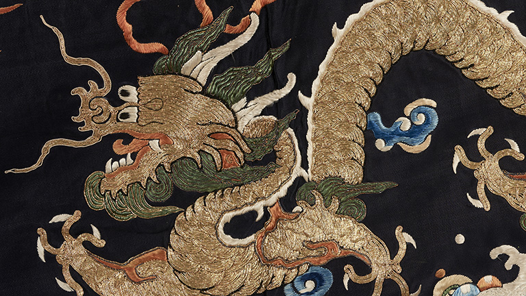 embroidered dragon in gold on a dark blue background