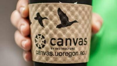 Coffee cup sleeve with Canvas logo and UO's Canvas URL: canvas.uoregon.edu