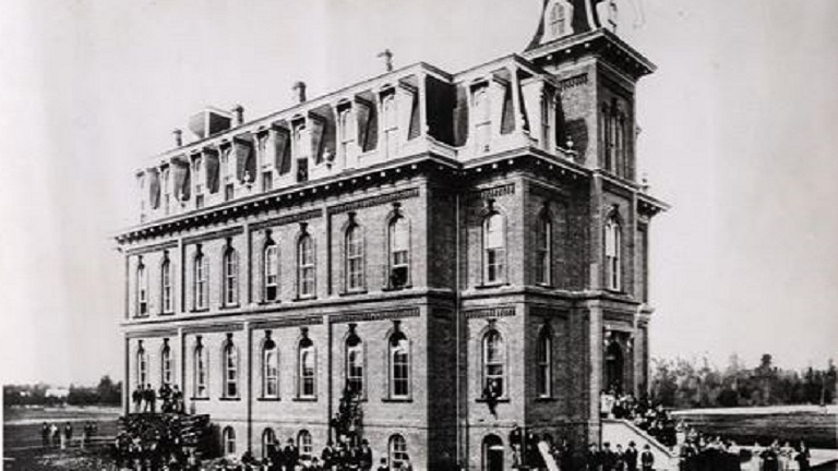 19th century photo of Deady Hall with crowd assembled outside