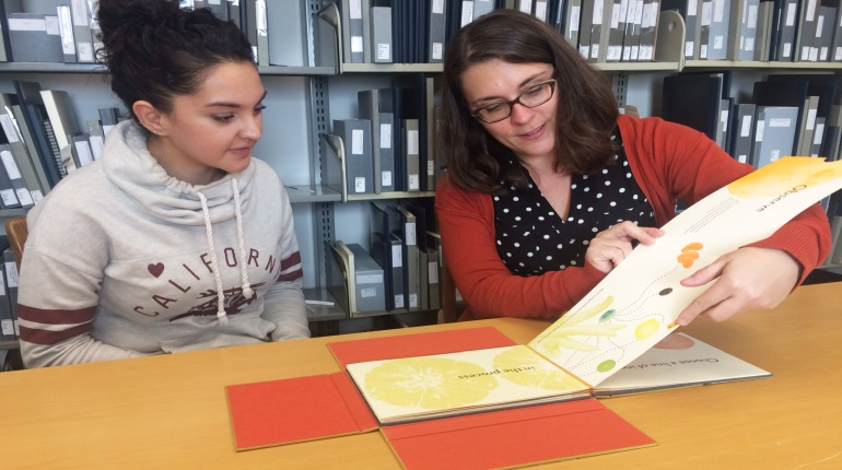 Student consults with librarian about artists' book research.