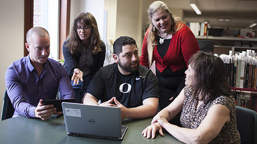 A group of five library staff using a laptop and tablet.