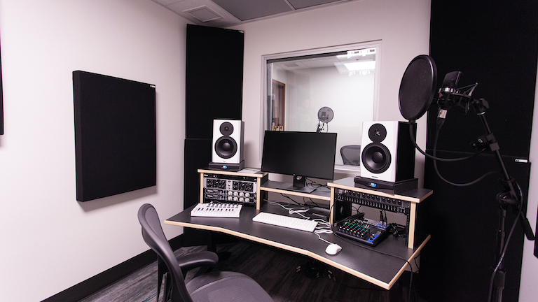 Photograph of the audio production space in the Douglas Room with computer, microphones, speakers, and equipment