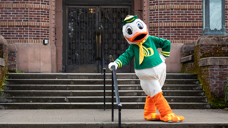 a photo of the Oregon Duck mascot on the front steps of Knight Library