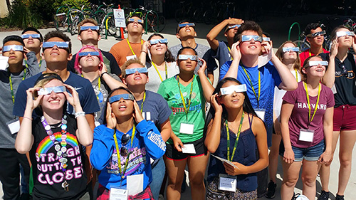 a group of students using eclipse glasses