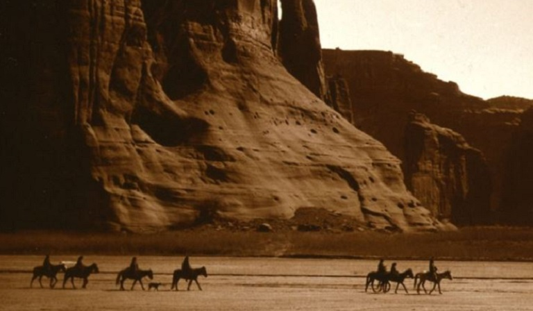 Sepia tone photo of Native Americans riding horses in desert southwest landscape