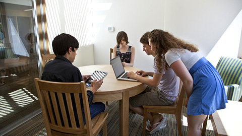 four students studying at a table