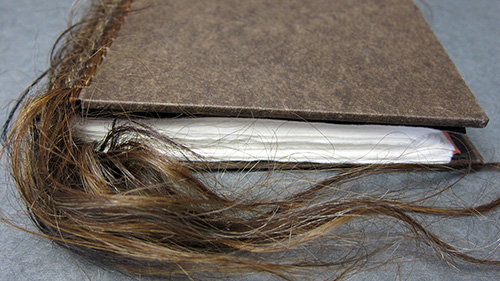"Photo of ""Hair Talk III,"" an artist's book in the A&AA library collection."