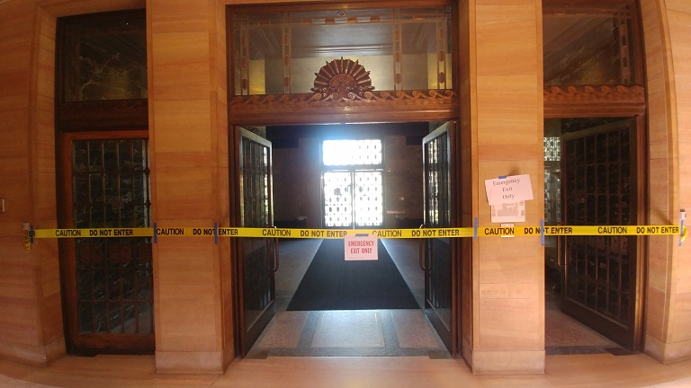 Entryway of Knight Library cordoned with yellow CAUTION tape