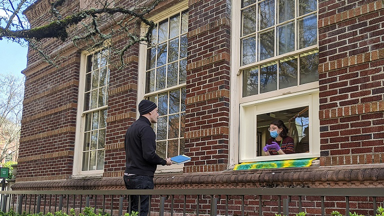 Library patron returning book to Knight Library pick-up window
