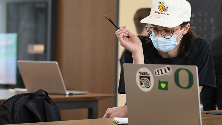 Student at laptop computer with hat and mask