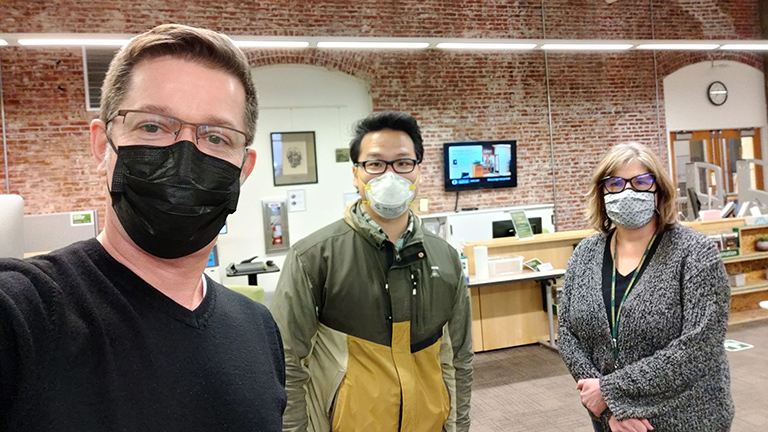Michael, Kevin, and Paula photographed with masks on in the Portland Library