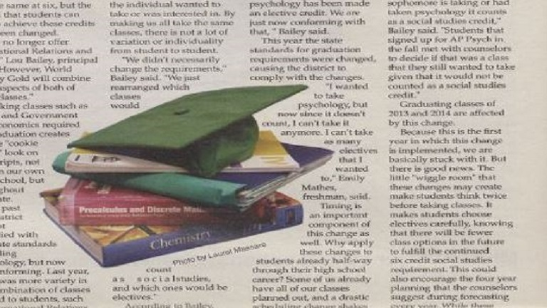 Close-up of newsprint page with stack of school books in photo