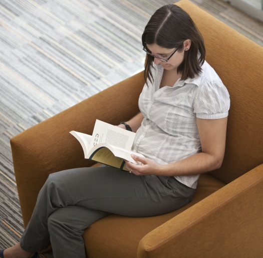 image: student studying in comfortable library chair
