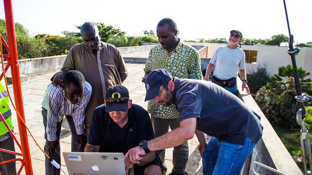 Phil Regnauld (NSRC), Ermanno Pietrosemoli and Marco Zennaro of ICTP Italy working with network engineers to install a high-speed, point-to-point wireless link at the Université Cheikh Anta Diop in Dakar, Senegal.