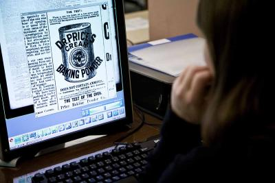 Patron viewing digitized historic newspaper content on computer screen