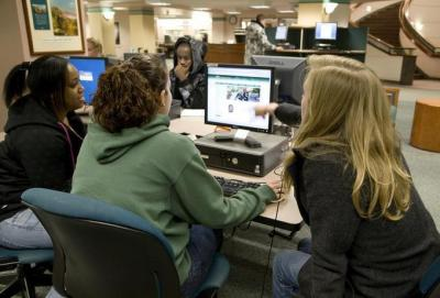 Female students working at library computer workstations