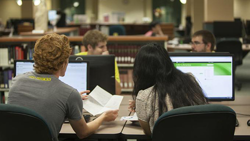 Two students at computers in the library