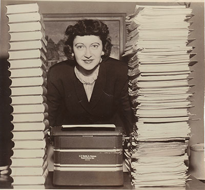 Sitcom pioneering Peg Lynch with typewriter and huge pile of scripts