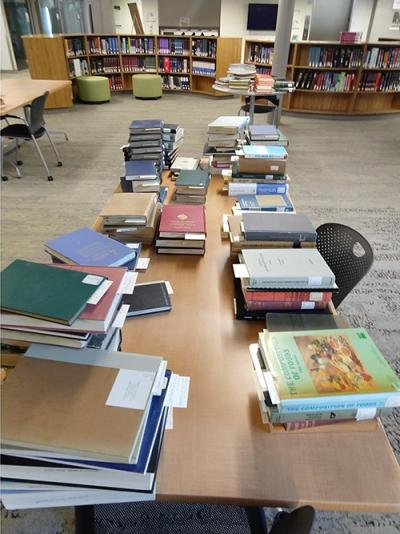 stacks of books on a table in the science library