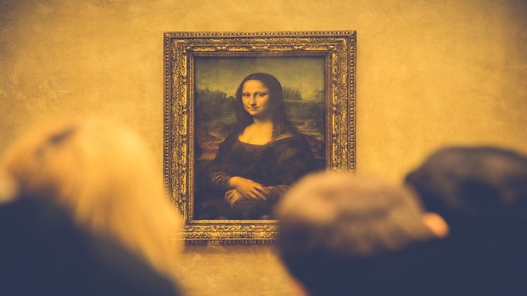 People looking at the Mona Lisa on museum wall.