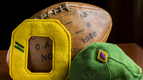 Image of University of Oregon memorabilia: football, jacket letter, and hat