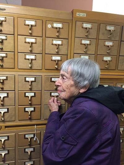 Ursula K. Le Guin standing next to library card catalog