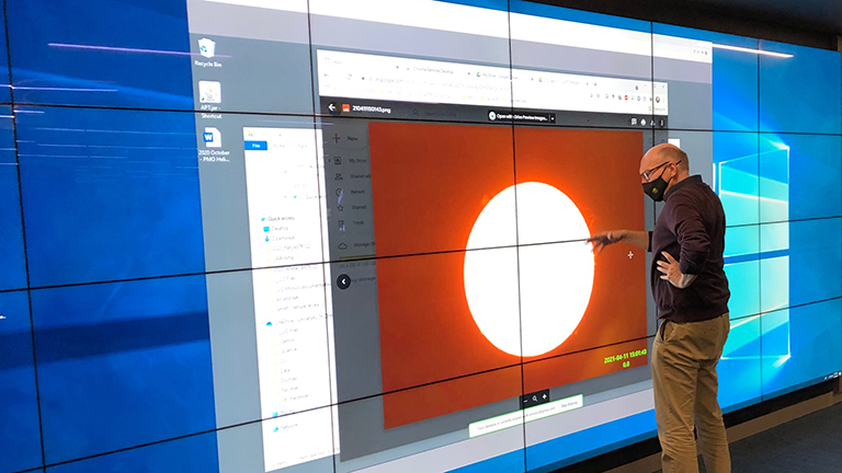 man looking at solar image in visualization lab